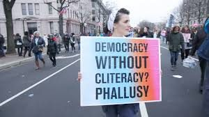 "An artist marches in a demonstration with a sign that says, ""Democracy without cliteracy? Phallusy"""